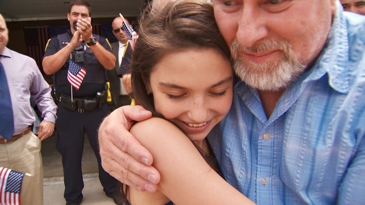 Sydney Dutton gets a hug from Paul Wilson of the Rochester Police Benevolent Assn.