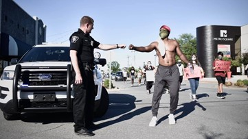 Photographer captures powerful fist-bumping moment between protestor and Conway police
